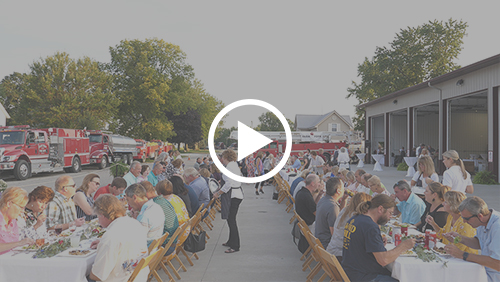 Two long tables outdoors filled with people