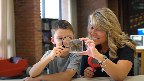 Woman looking at butterfly with young boy in library