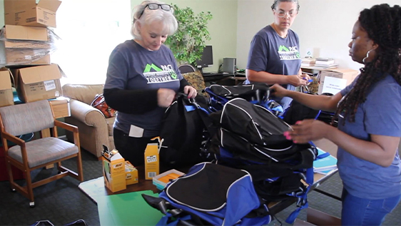 Bankers stuffing backpacks with supplies
